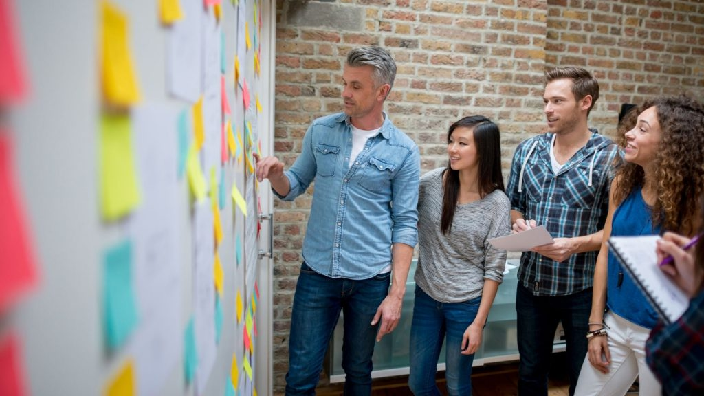 group brainstorming by a wall of sticky notes