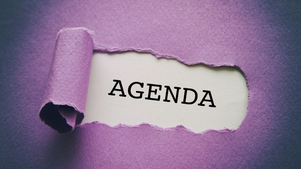 """the word """"Agenda"""" being uncovered behind purple paper"""