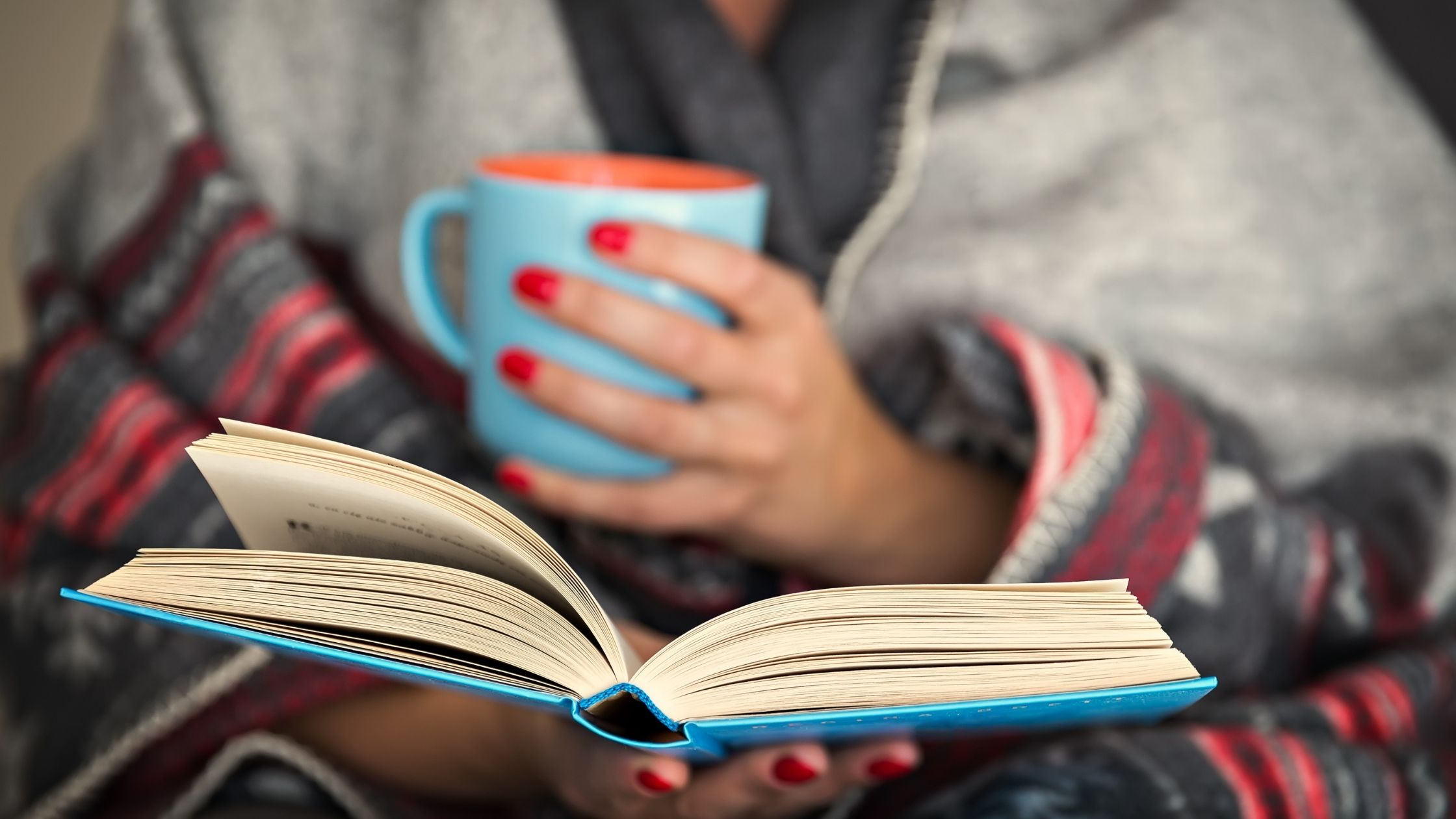 person holding a mug and reading a book